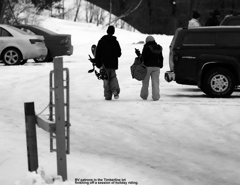 An image of a snowboarder and companion heading to their vehicle in the Timberline parking area at Bolton Valley Ski Resort in Vermont