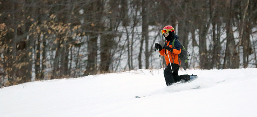 An image of Dylan Telemark skiing in powder at Bolton Valley Ski Resort in Vermont