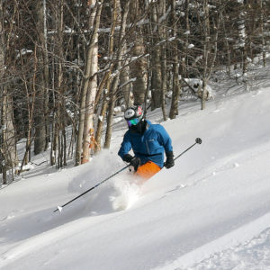 An image of Ty skiing powder on the Spell Binder trail at Bolton Valley Resort in Vermont