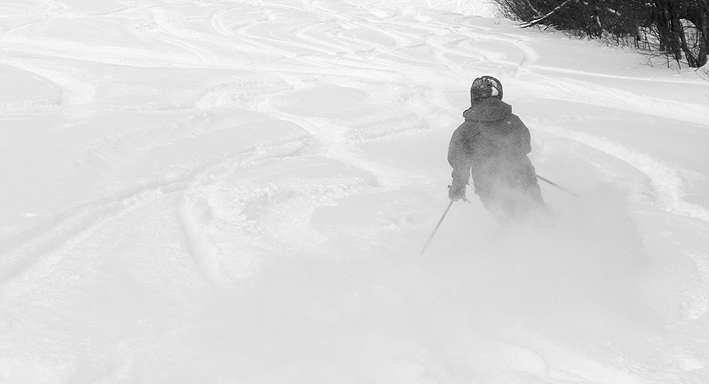 An image from behind of Ty skiing powder on the Tattle Tale trail at Bolton Valley Resort in Vermont