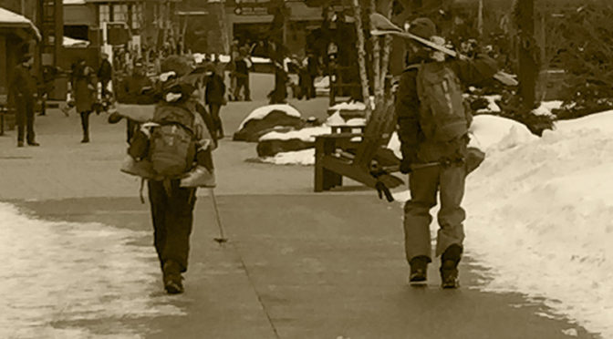 An image of Ty and Dylan walking through the Spruce Peak Village with their skis and gear at Stowe Mountain Resort in Vermont