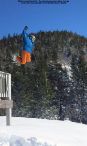 An image of Ty taking a huge jump off the railing of the Wilderness Summit Ski Patrol Hut into deep powder below at Bolton Valley Resort in Vermont
