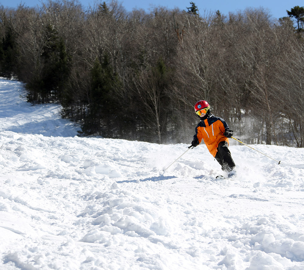 An image of Dylan Telemark skiing in chopped up snow on the Tattle Tale trail at Bolton Valley Resort in Vermont