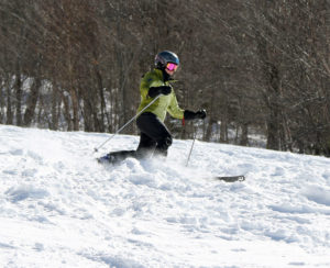 An image of Erica Telemark skiing chopped up snow on the Tattle Tale trail at Bolton Valley Resort in Vermont