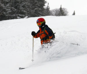 An image of Dylan skiing powder on the Tattle Tale trail at Bolton Valley Resort in Vermont