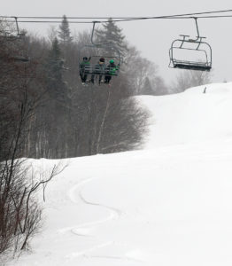 An image of skiers on the Timberline Chairlift at Bolton Valley ski resort on Vermont