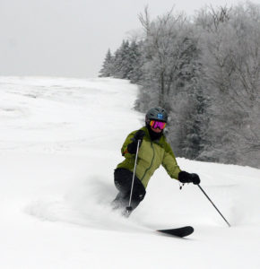 An image of Erica Telemark skiing in powder at Bolton Valley Resort in Vermont