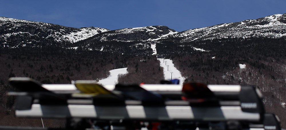 An image of Mt. Mansfield in above a ski rack on a clear day in the spring at Stowe Mountain Resort in Vermont