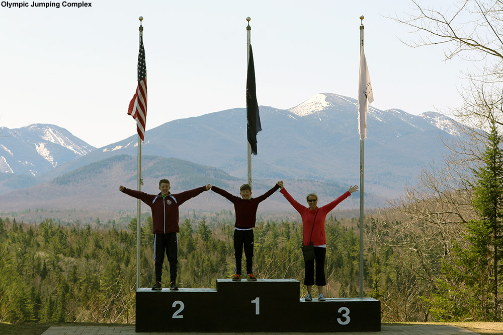 An image of Erica and the boys on the podiums at the Lake Placid Olympic Jumping Complex