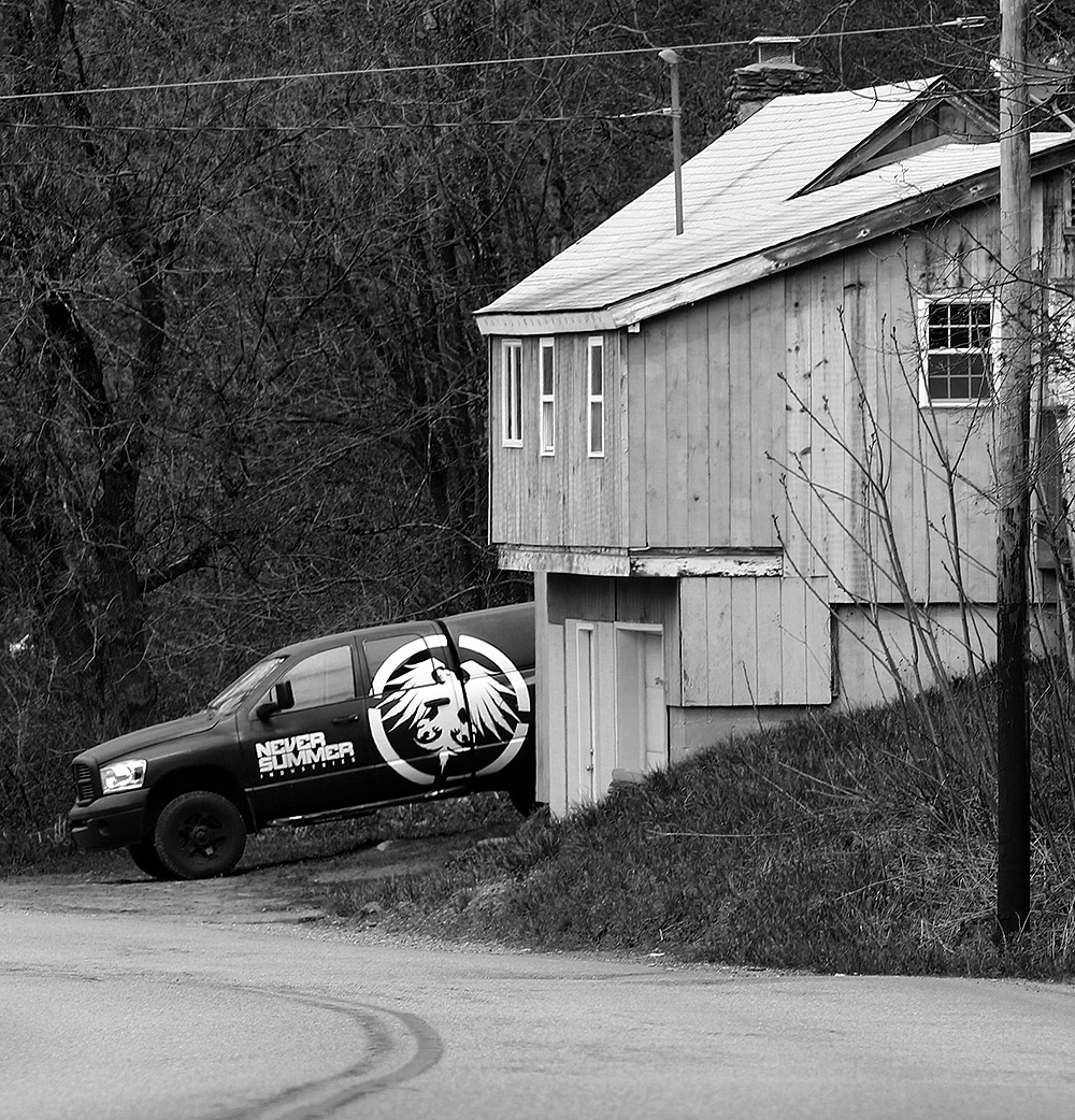 "An image of a house with a ""Never Summer"" truck along the route to Stowe in Moscow, Vermont"