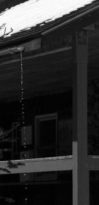 An image of water pouring from a gutter at the Hermit Lake Caretaker's Cabin near Mt. Washington in New Hampshire
