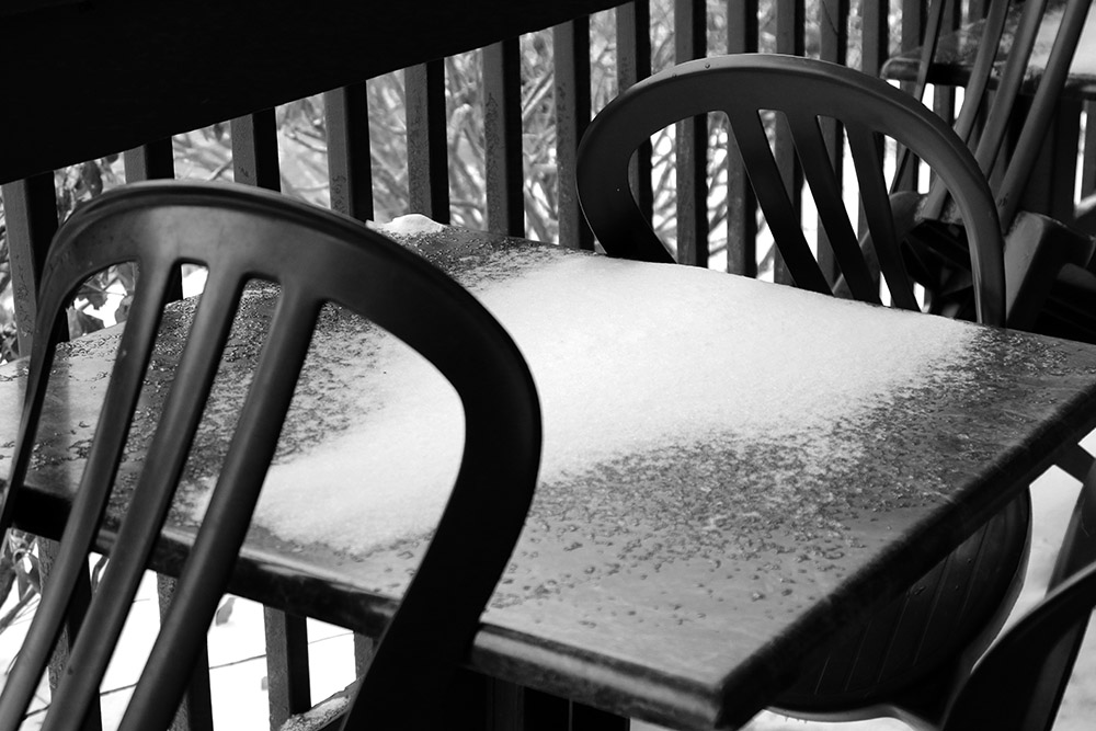 An image of snowy chairs on the deck in front of the Deli in the Bolton Valley Village at Bolton Valley Ski Resort in Vermont