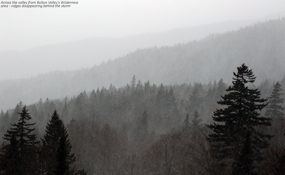 An image of ridgelines in the Bolton Valley Reosrt area in Vermont disappearing behind snow from a December storm