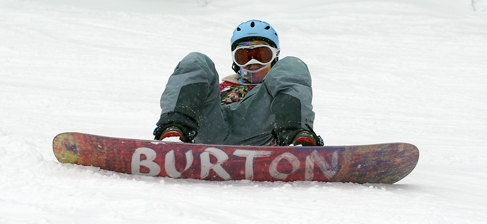 An image of Molly waiting on the trail on her snowboard at Stowe Mountain Resort in Vermont