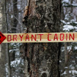 An image of a sign on the Bryant Trail indicating the direction of Bryant Cabin at Bolton Valley Ski Resort in Vermont