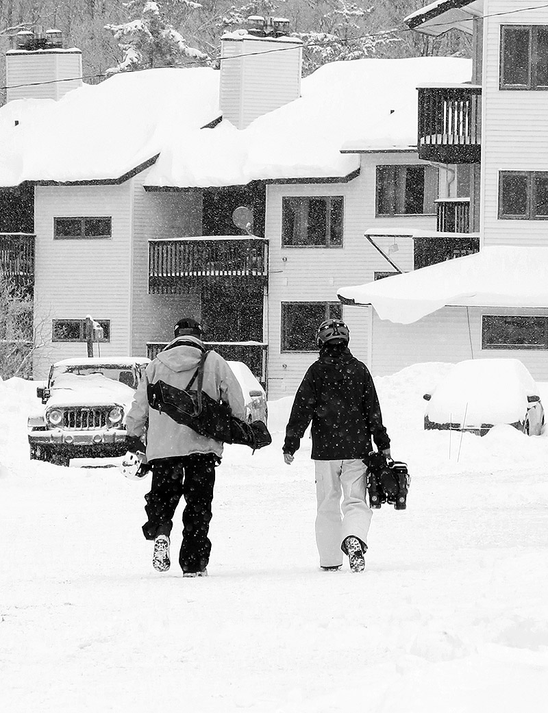 An image of two skiers walking through snowfall in the Village at Bolton Valley Ski Resort in Vermont