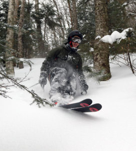 An image of Wiley skiing powder in the Hazelton Zone at Stowe Mountain Resort in Vermont