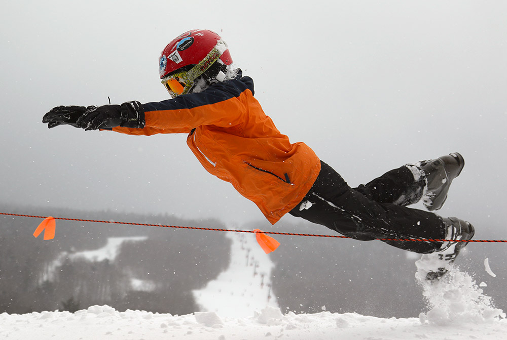 An image of Dylan jumping into powder at Stowe Mountain Resort
