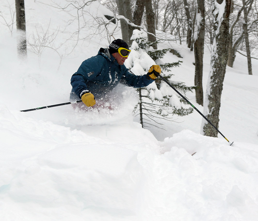 An image of Dave skiing waist deep powder at Stowe Mountain Resort in Vermont