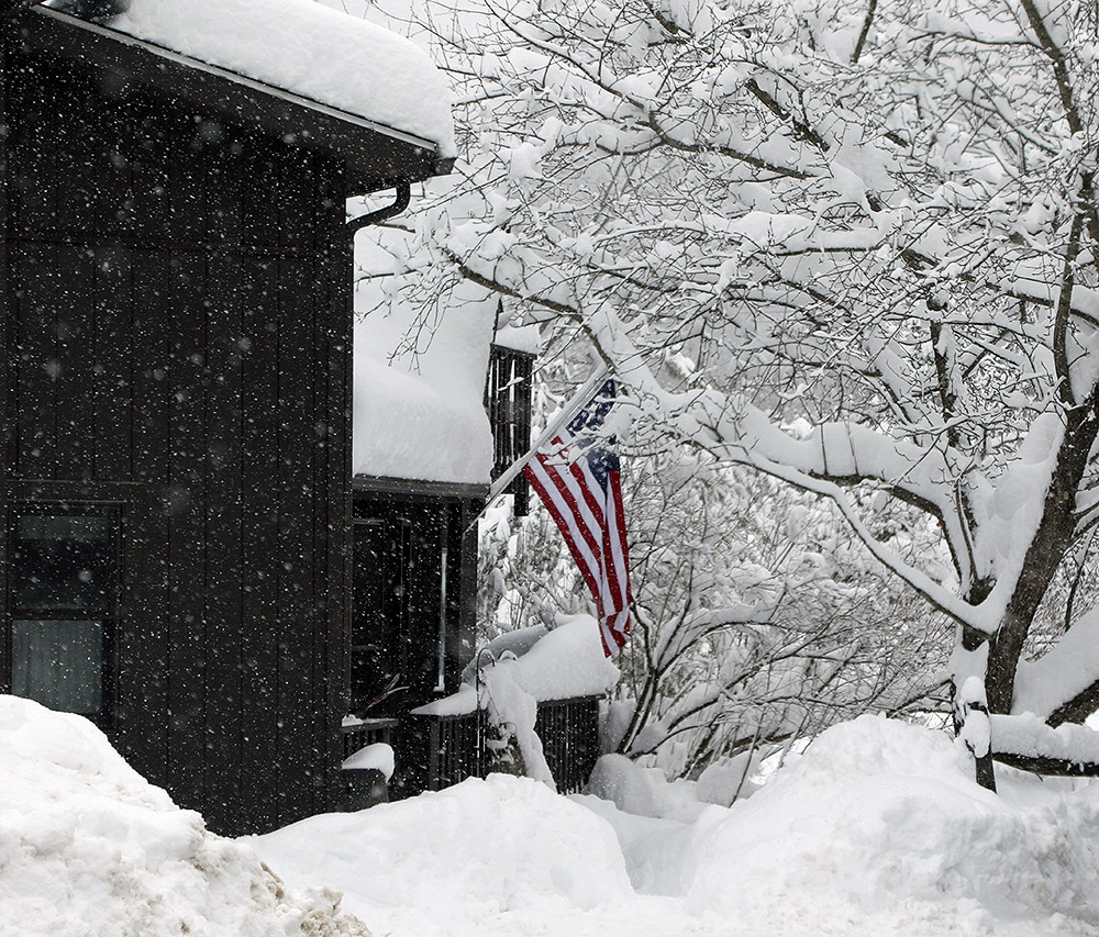 An image of a house with fluffy snow accumulations along the Bolton Valley Access Road near Bolton Valley Ski Resort in Vermont