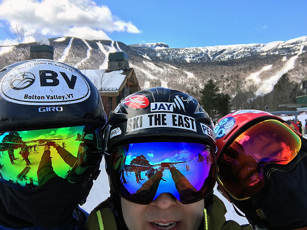 an image of Ty, Jay, and Dylan wearing Anon M2 goggles with various lenses with the trails of Stowe Mountain Resort in Vermont in the background