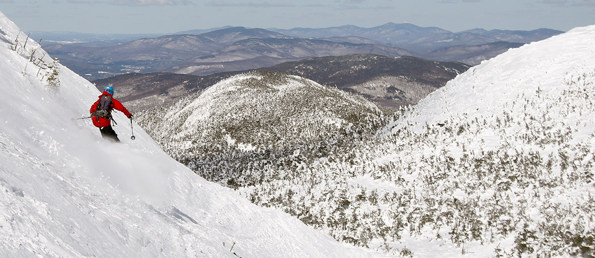 An image of Jonah skiing Mt. Mansfield below the Hourglass Chute with the Mt. Mansfield Adam's Apple in the background