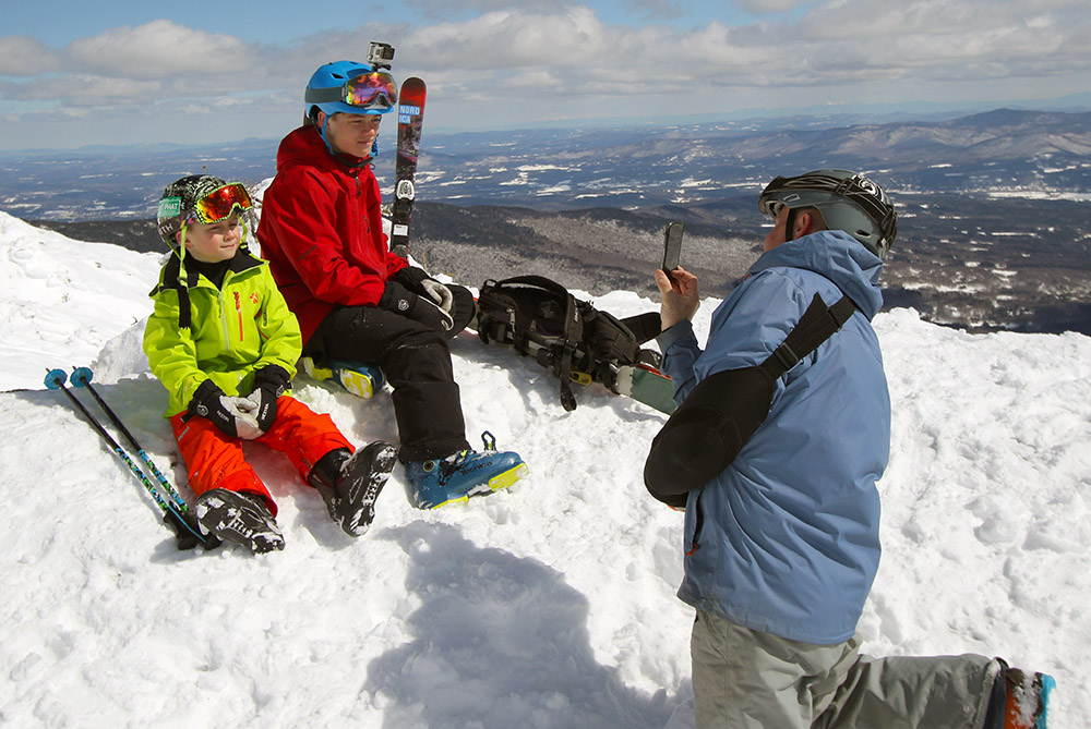 An image of Josh taking a photo of Agi and Jonah on the Mt. Mansfield ridgeline during an ascent to the Chin of Mt. Mansfield in Vermont