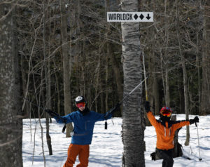 An image of Ty and Dylan underneath the sign for the Warlock trail at Magic Mountain in Vermont