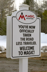 "An image of a sign at Magic Mountain Ski Area in Vermont stating ""You've now officially take the road less traveled - Welcome to Magic"""