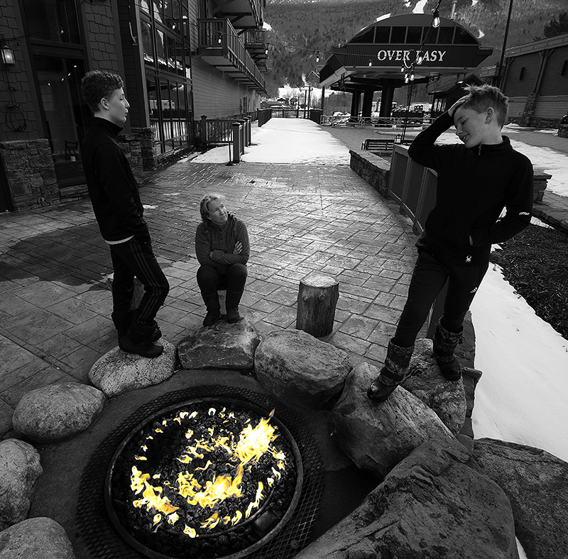 Erica, Ty, and Dylan standing around the fire pit outside the Solstice Restaurant at Stowe Mountain Resort in Vermont