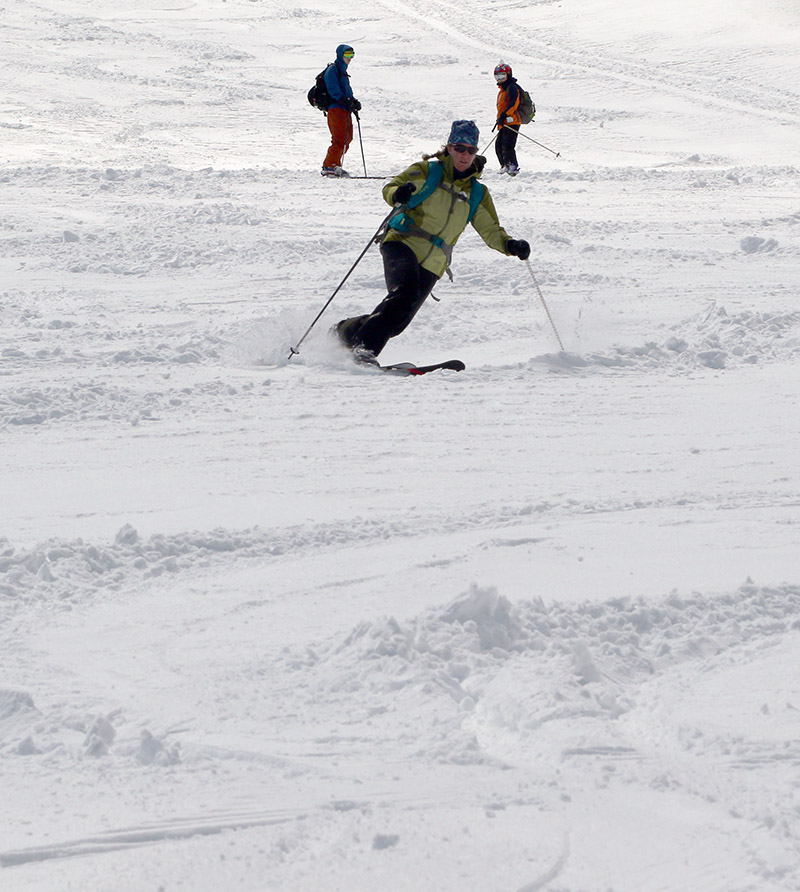 An image of Erica skiing some fresh snow on the Nosedive trail at Stowe Mountain Resort in Vermont with Ty and Dylan looking on