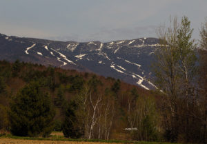 An image of the snowy ski trails on Mountain Mansfield at Stowe Mountain Resort in Vermont in mid May