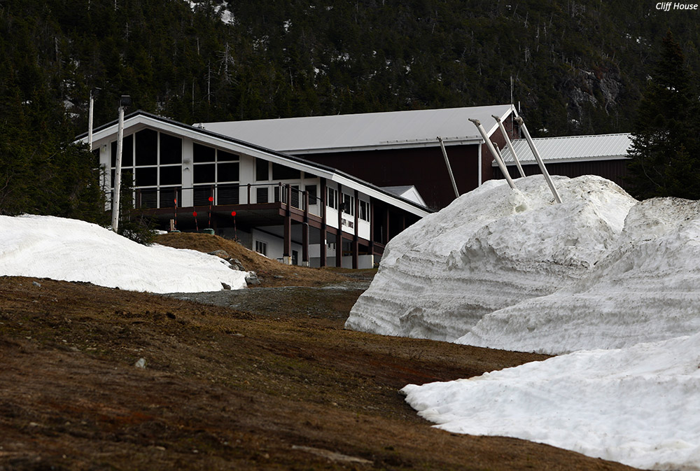 An image of deep snow piles in May up on Mt. Mansfield at the Cliff House after work road plowing by Stowe Mountain Ski Resort in Vermont