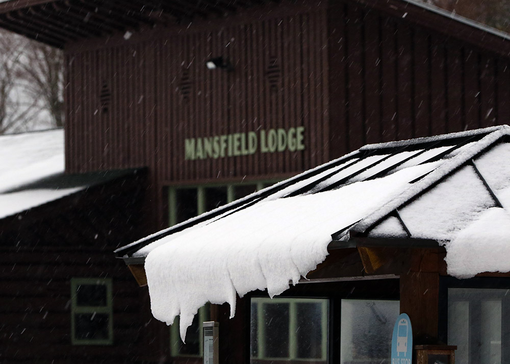 An image of snow sliding off a roof in front of the Mansfield Base Lodge at Stowe Mountain Resort in Vermont as an October nor'easter affects New England