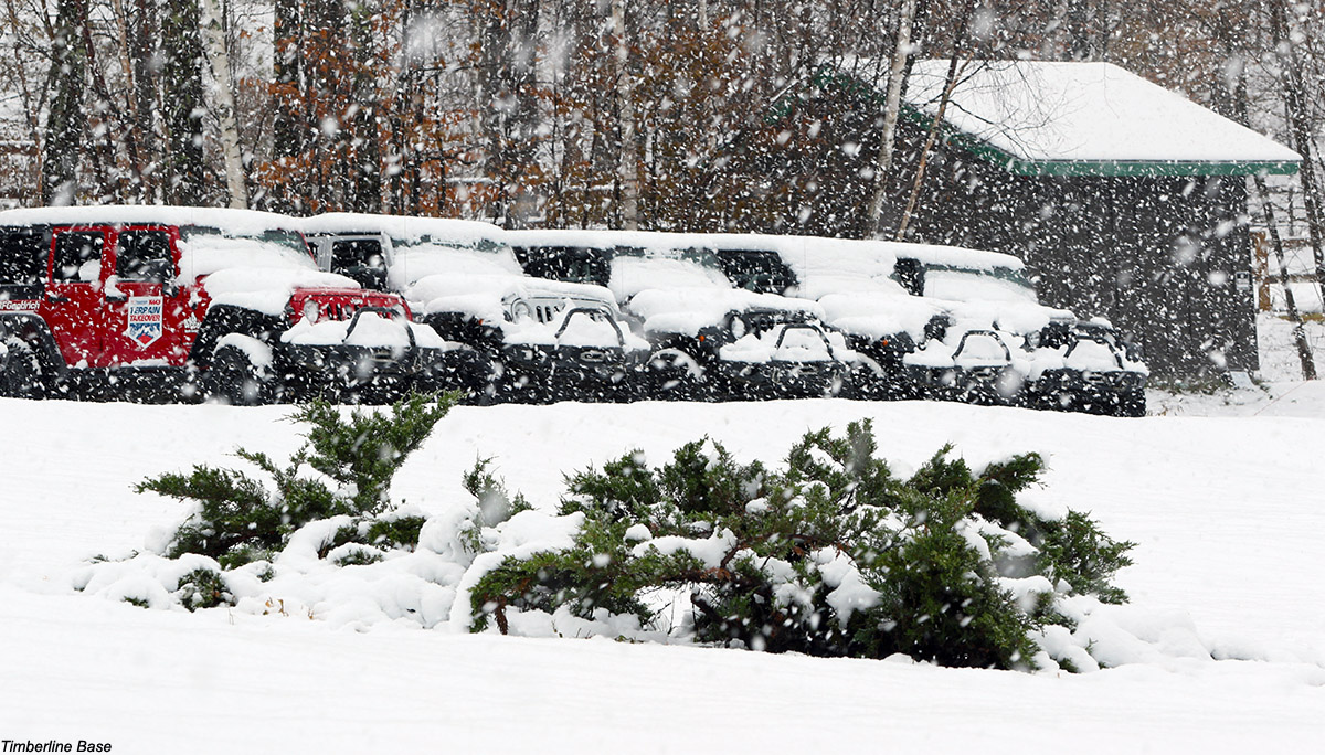 An image showing some of the four-wheel drive vehicles parked at the Timberline base area of Bolton Valley Resort in Vermont as heavy snowfall fills the arir from a November snowstorm