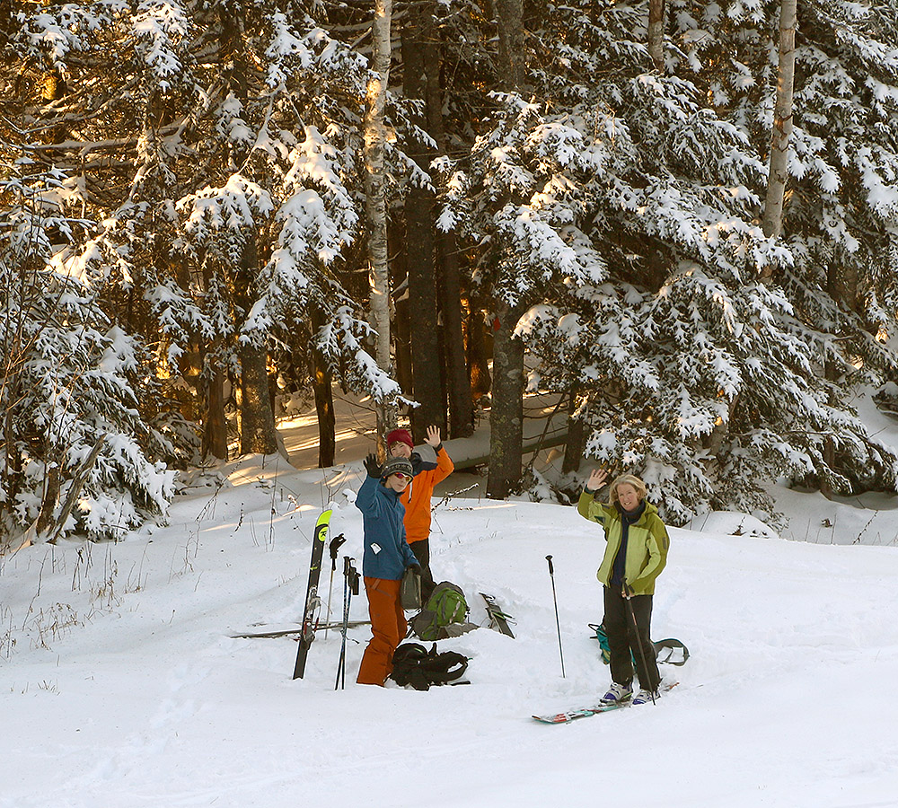 An image of Erica, Ty, and Dylan waving hello on their first ski tour of the season at Bolton Valley Resort in Vermont