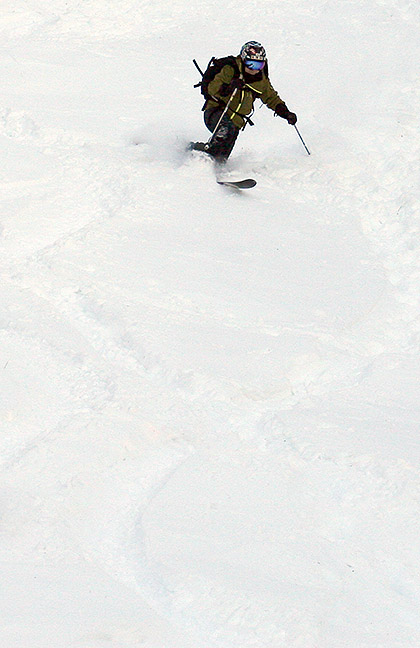 An image of Jay Telemark skiing in powder from a November snowstorm at Bolton Valley Ski Resort in Vermont