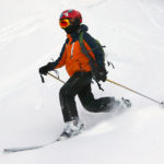 An image of Dylan Telemark skiing in powder after a November snowstorm at Bolton Valley Ski Resort in Vermont