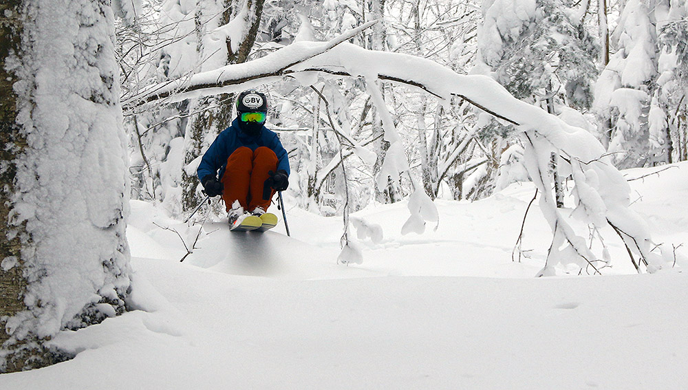 An image of Ty skiing powder and ducking under a bent tree in the Snow Hole area of Bolton Valley Resort in Vermont