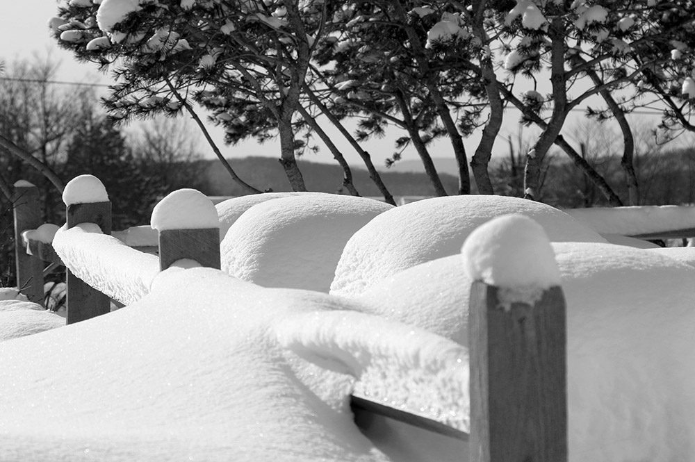 An image of snow on railings and tables in the Village at Bolton Valley Ski Resort in Vermont