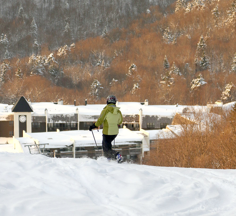 An image of Erica skiing at Bolton Valley Ski Resort with Bolton Valley Village in the background
