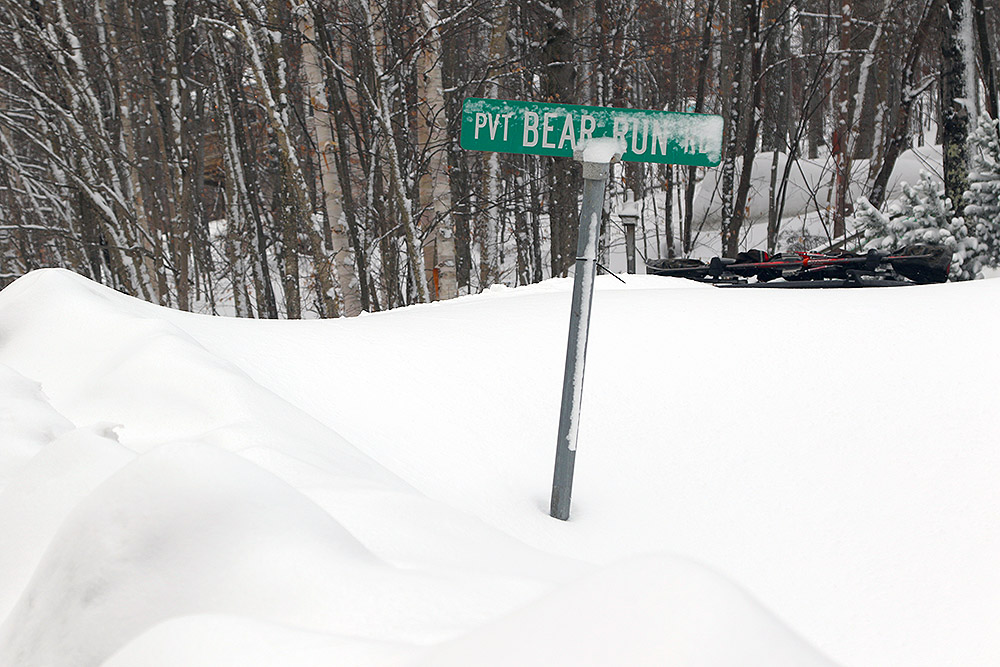 An image of the Bear Run street sign in deep snowbanks along the Bolton Valley Access Road near Bolton Valley Ski Resort in Vermont