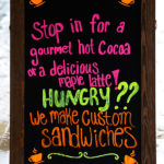 An image of a sign announcing custom made sandwiches and maple lattes at the Village Deli at Bolton Valley Ski Resort in Vermont