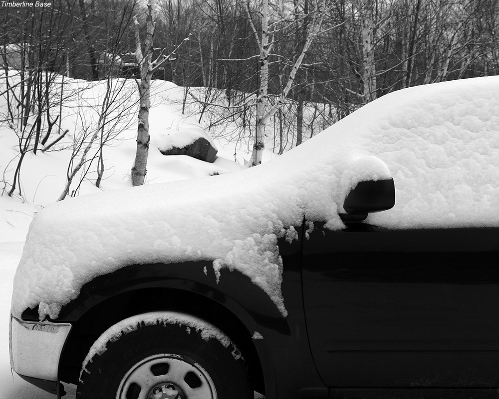 An image of a car with fresh snow on it in the parking area near the Timberline Base Lodge at Bolton Valley Ski Resort in Vermont