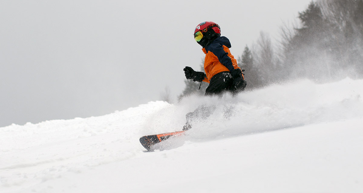 An image of Dylan slashing through some powder on his snowboard at Stowe Mountain Resort in Vermont