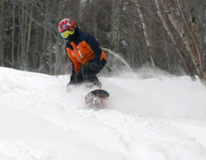 An image of Dylan snowboarding in powder on Upper Meadows at Stowe Mountain Resort in Vermont