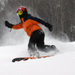 An image of Dylan snowboarding in soft snow at Stowe Mountain Resort in Vermont