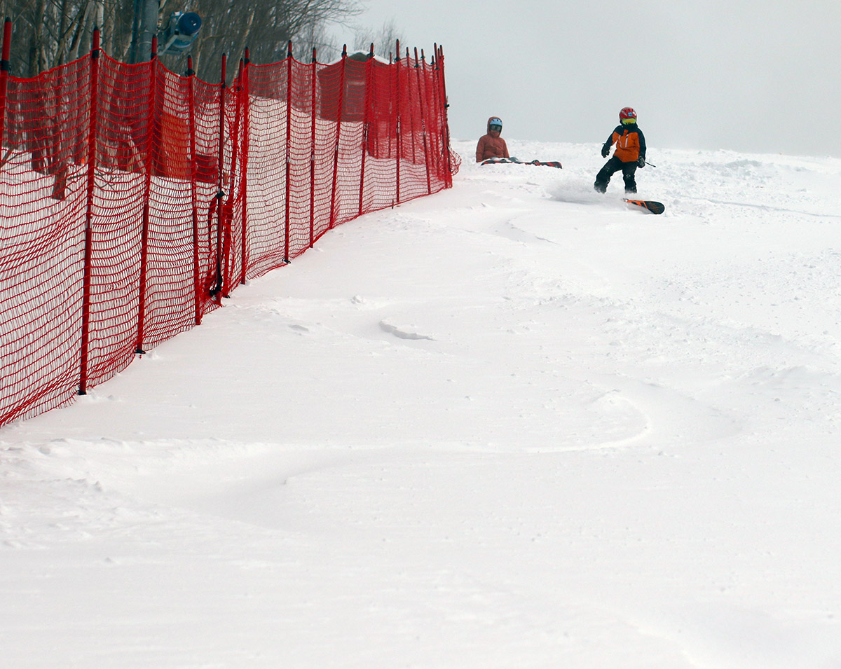 An image of Dylan and Molly getting ready to ride their snowboards in some powder on the Competition Hill area of Spruce Peak at Stowe Mountain Resort in Vermont