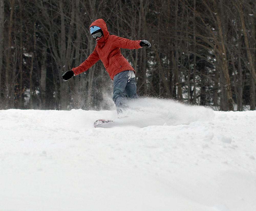 An image of Molly snowboarding in powder on the Upper Meadows trail at Stowe Mountain Resort in Vermont