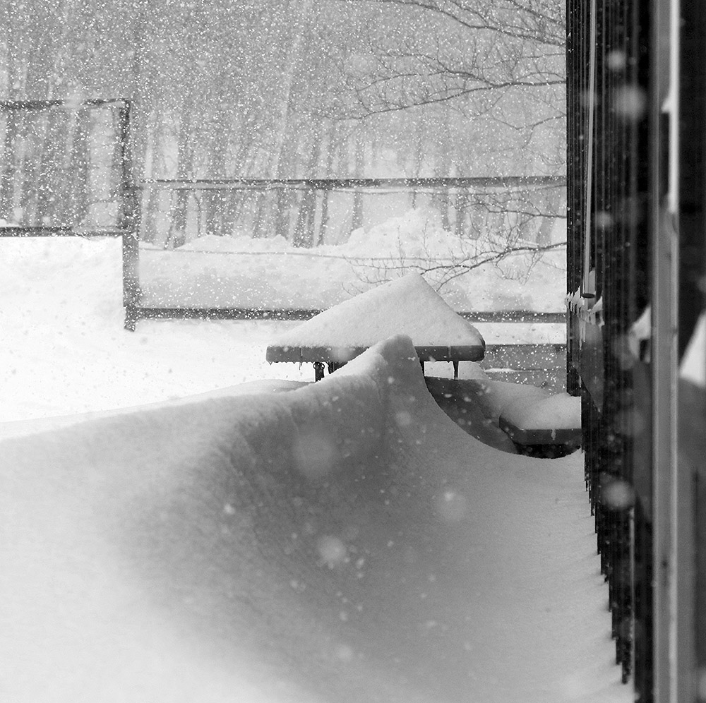 An image of drifted snow and some heavy snowfall behind the Timberline Base Lodge at Bolton Valley Ski Resort in Vermont